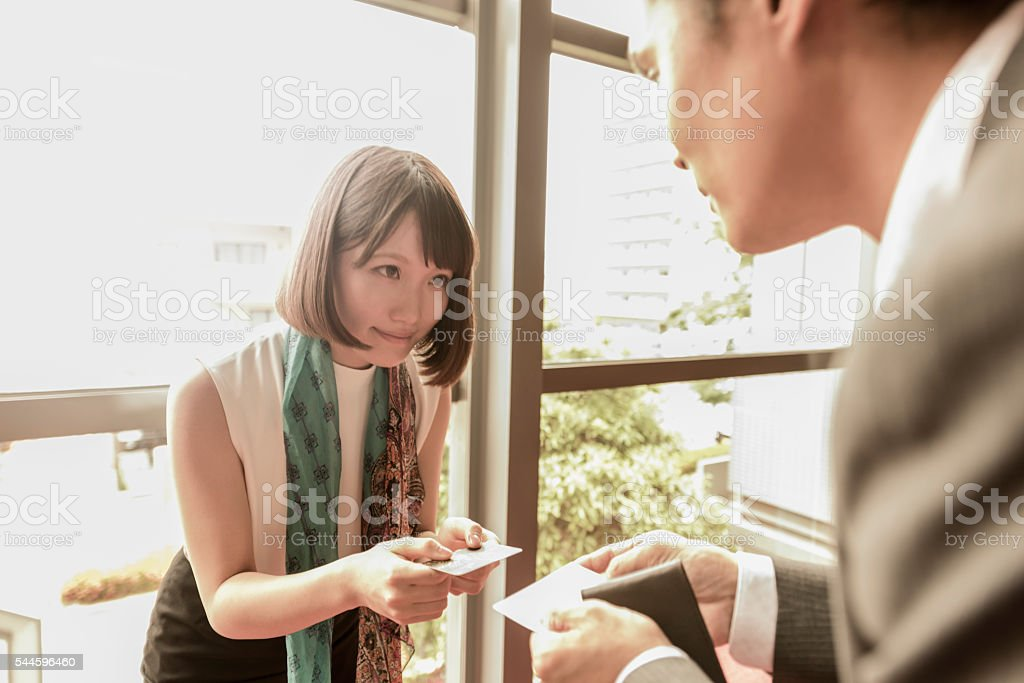 Young Japanese woman handing over business card to colleague stock photo
