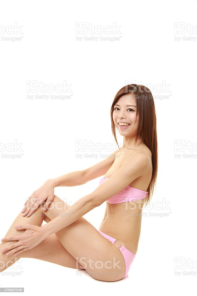 young Japanese woman in a pink bikini with smooth legs stock photo