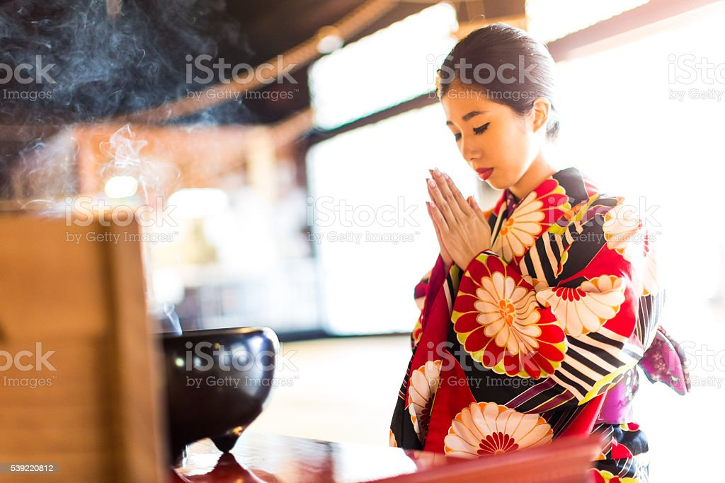 Young Japanese Woman Praying at Hyakumanben Chionji Temple, Kyoto, Japan stock photo