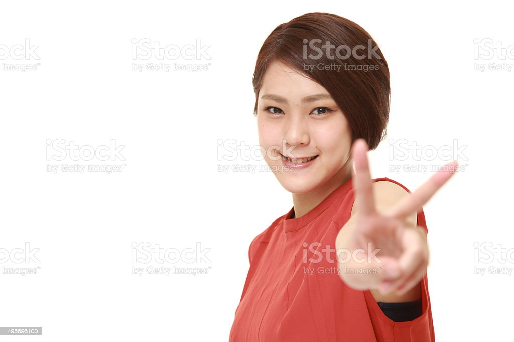 young Japanese woman showing a victory sign stock photo