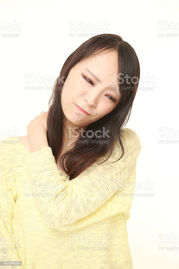 young Japanese woman suffers from neck ache stock photo