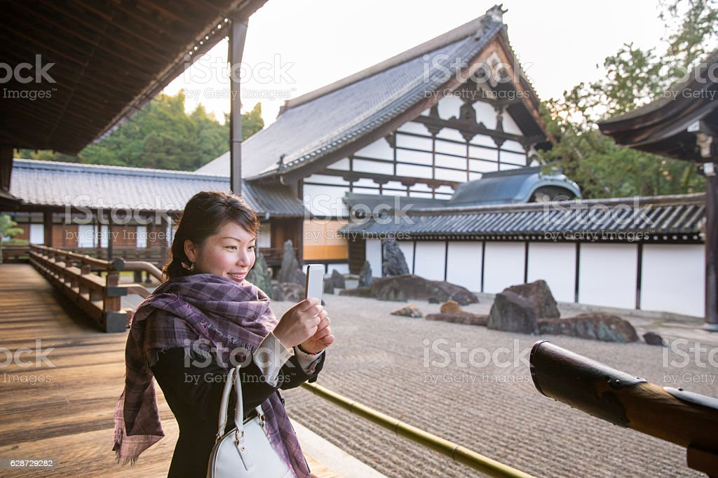 Young Japanese woman taking pictures in stone garden in temple stock photo