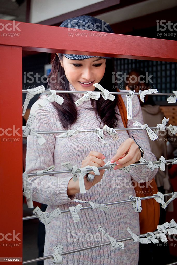 Young Japanese woman tying fortune paper stock photo