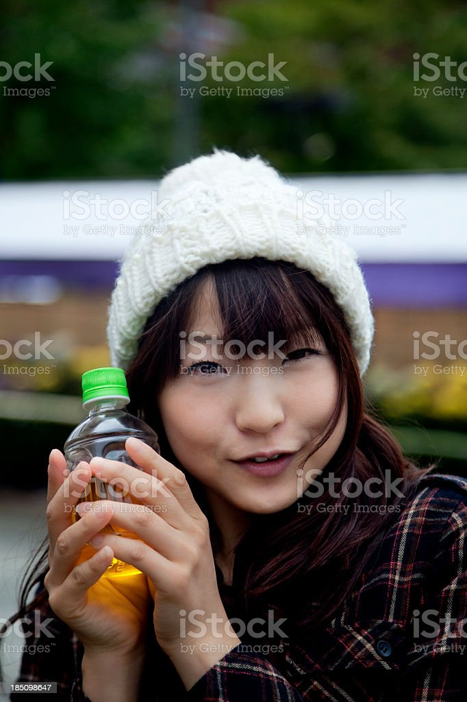 Young Japanese woman with green tea bottle on cold day royalty-free stock photo