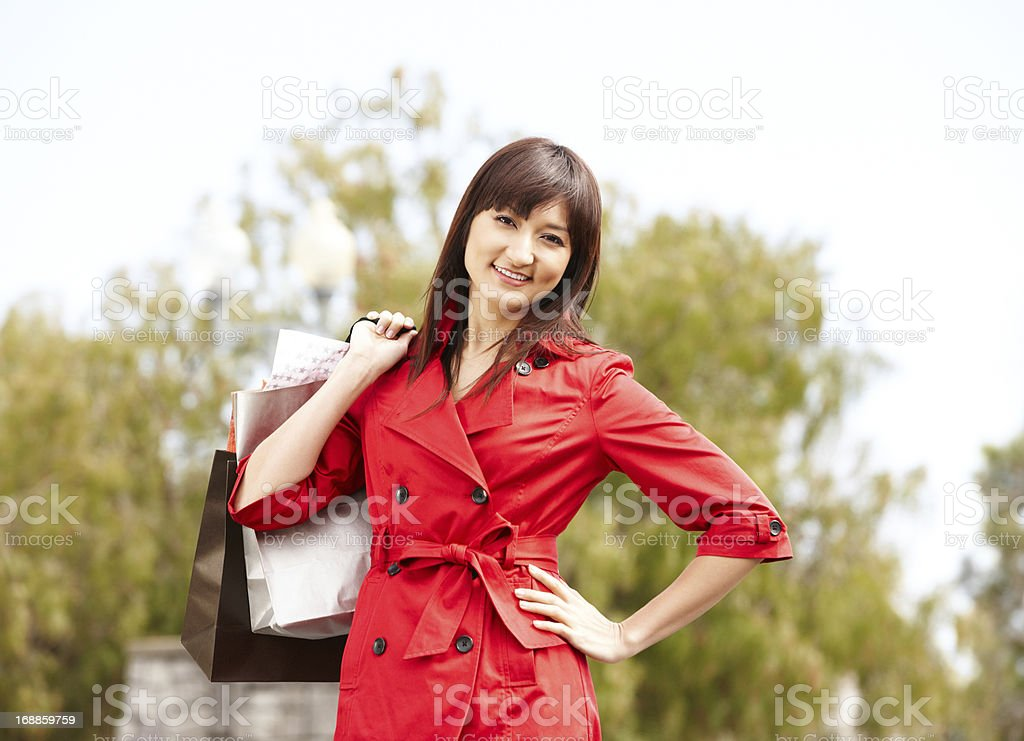Young Japanese woman with shopping bags outdoors royalty-free stock photo