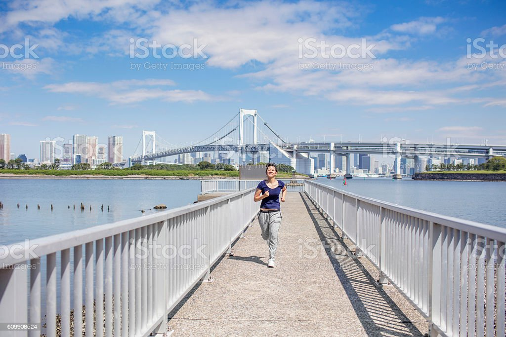 Young Japanese women running in a pier at Tokyo stock photo