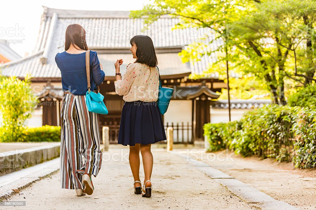 Young Japanese women walking the relaxing grounds of Buddhist temple stock photo
