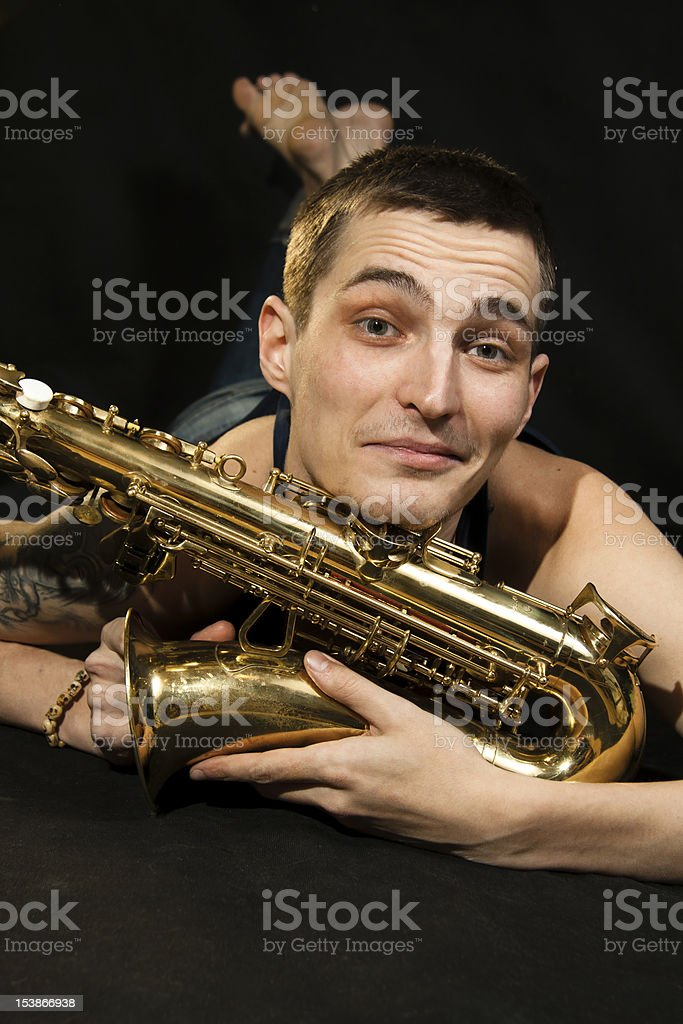 young jazzman lie on the floor with saxophone stock photo