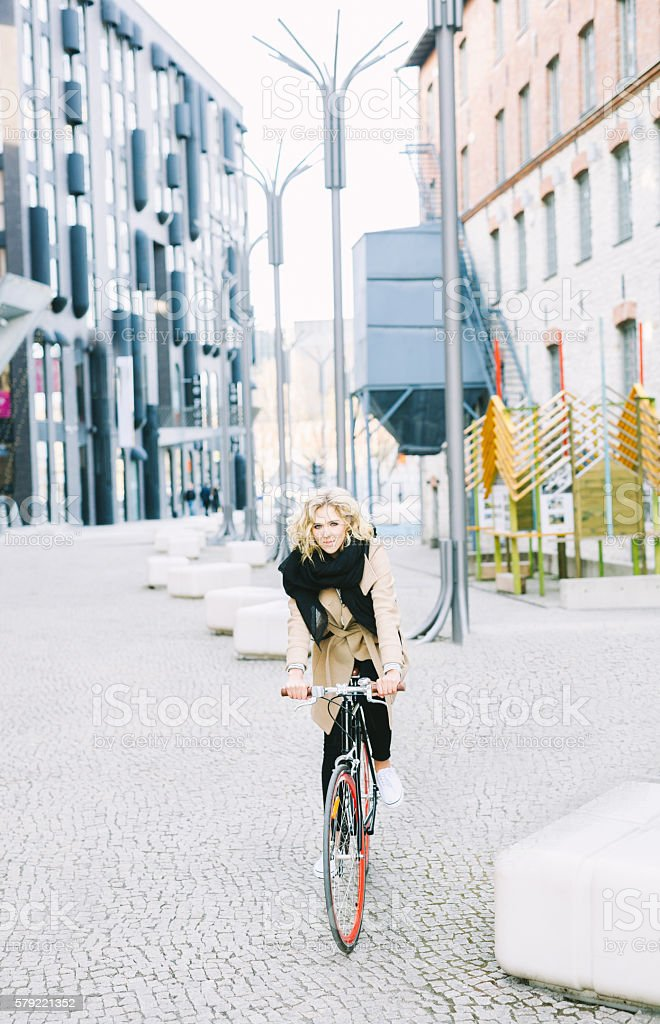 Young Joyful Woman Riding A Bicycle In Modern Shopping District stock photo