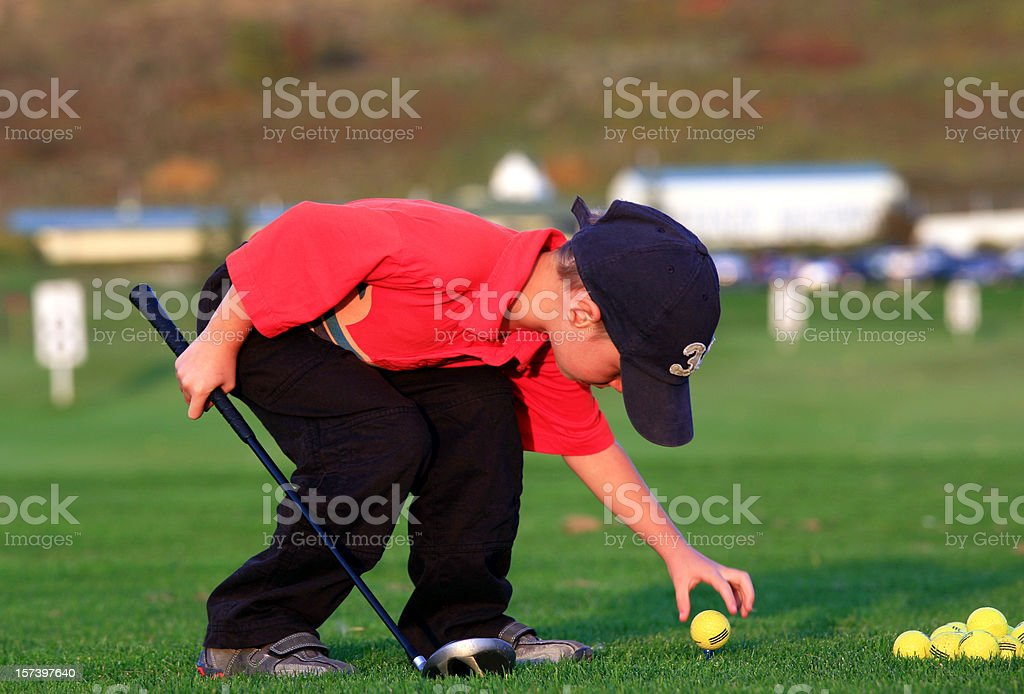 Young Junior Golfer Teeing it Up stock photo