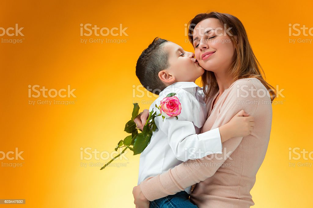 Young kid giving red rose to his mom stock photo