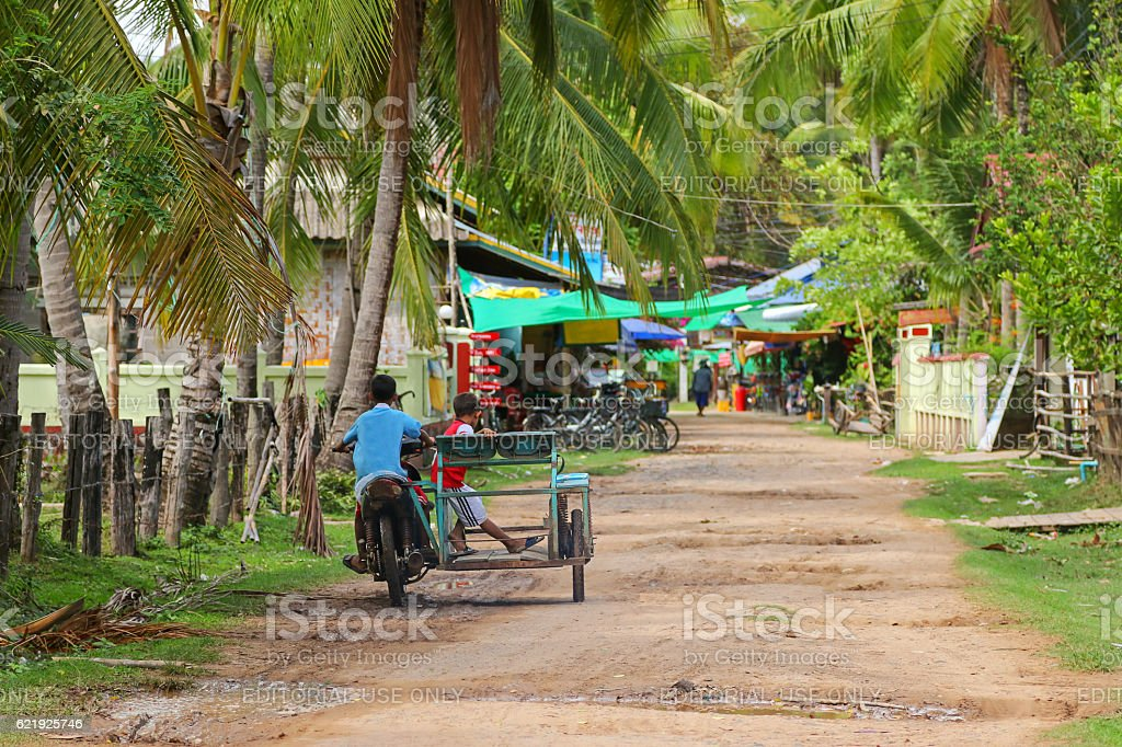 Young kids driving tricycle motorcycle on street in Champasak, Laos stock photo