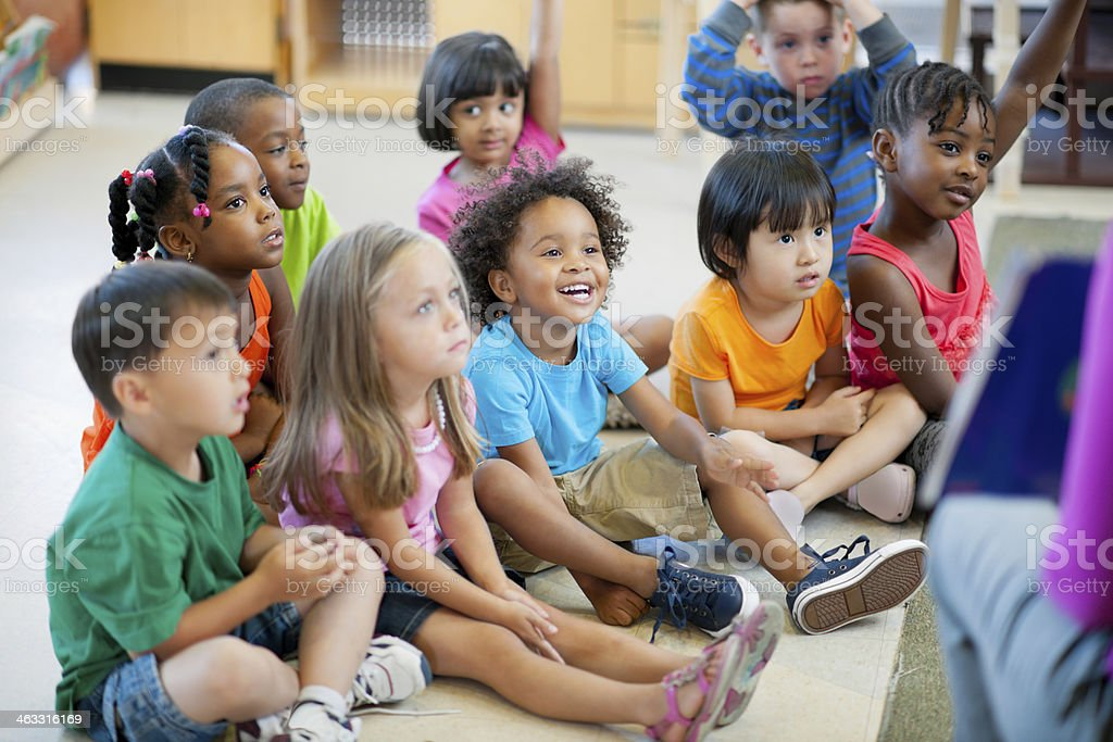 Young kids listening to teacher royalty-free stock photo