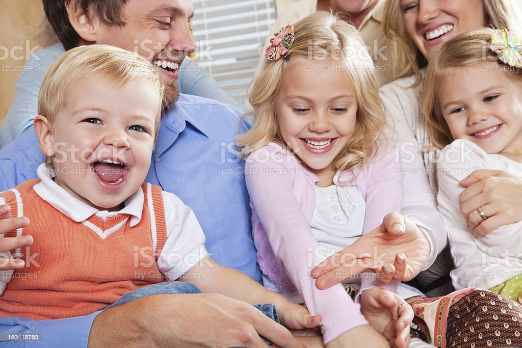 Young Kids Playing With Parents and Grandparents in Living Room royalty-free stock photo