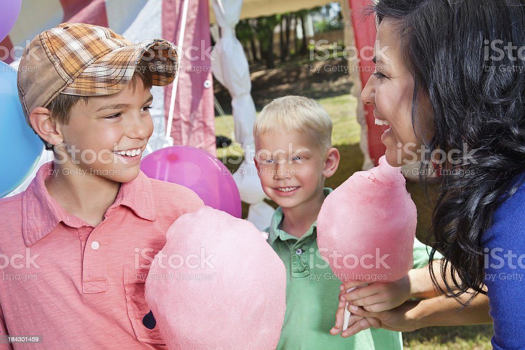 Young Kids Receiving Cotton Candy From Mom at Carnival royalty-free stock photo