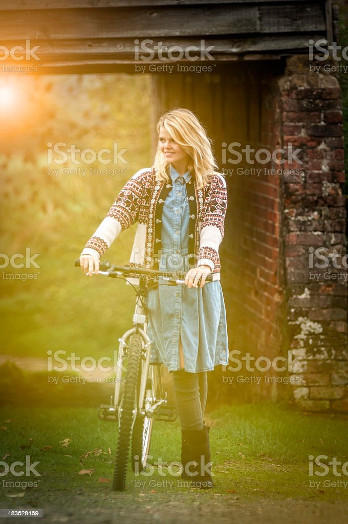 Young kinfolk woman with her bike at the sunset (V) stock photo