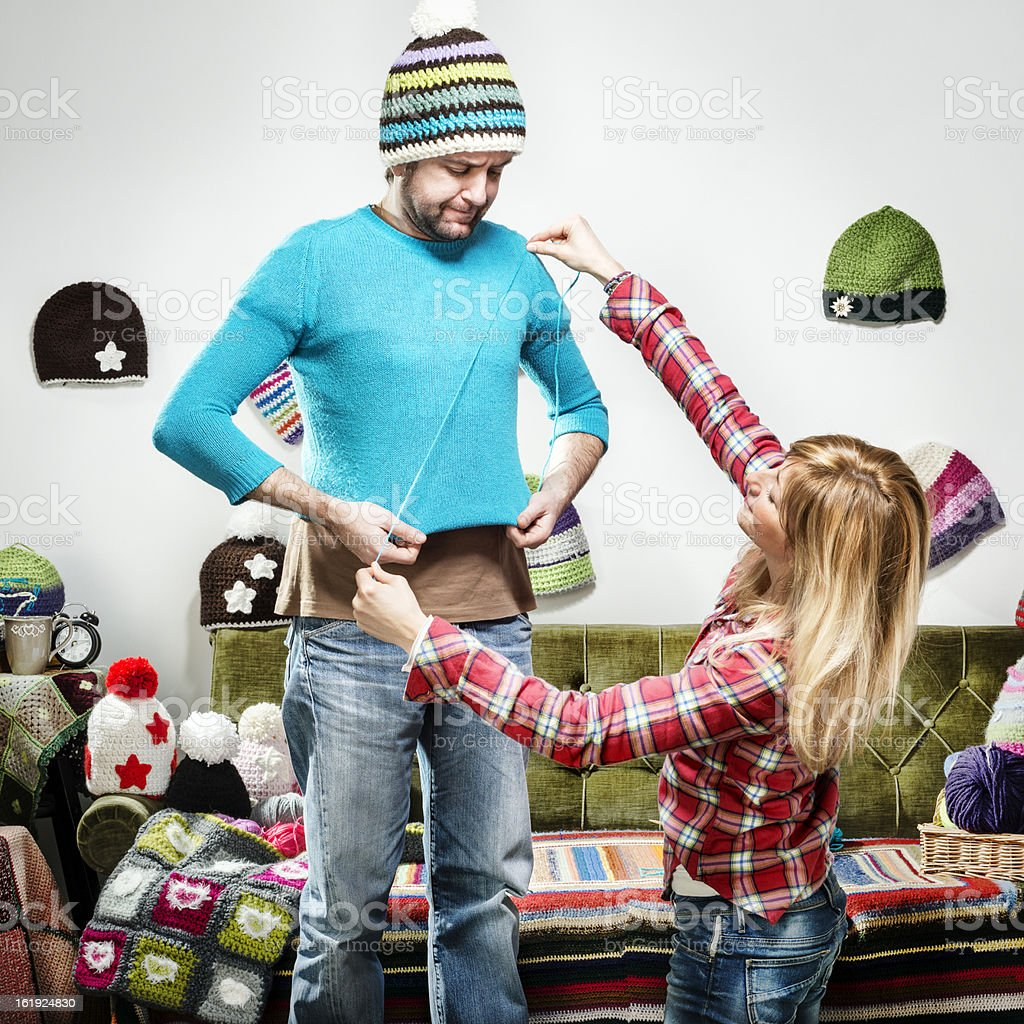 Young knitter woman sweater present for displeased boyfriend royalty-free stock photo