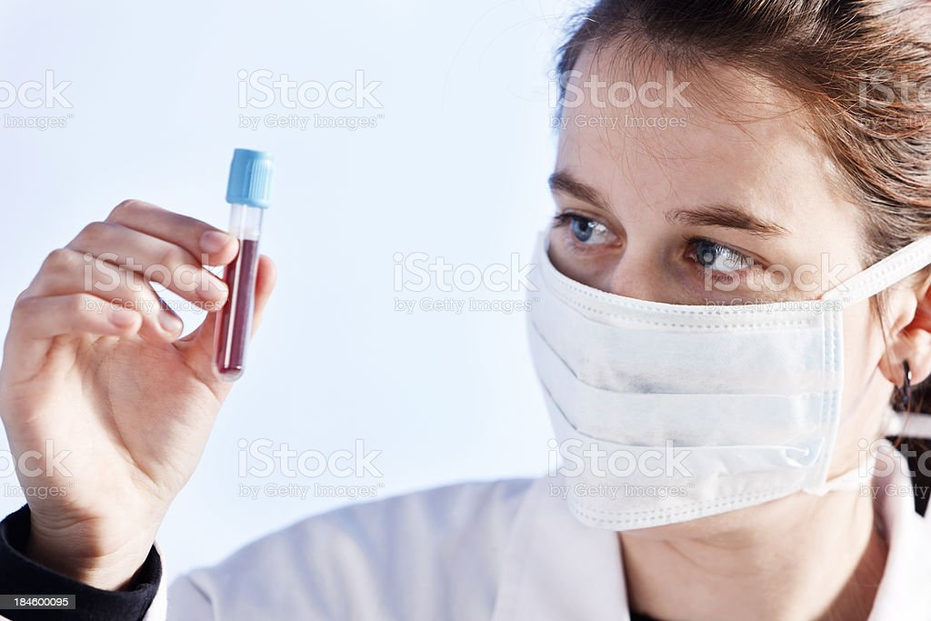Young lab technician examines medical specimen royalty-free stock photo