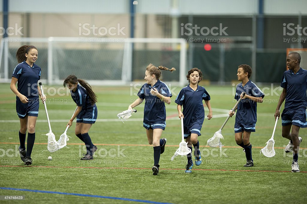 Young lacrosse team run on field stock photo