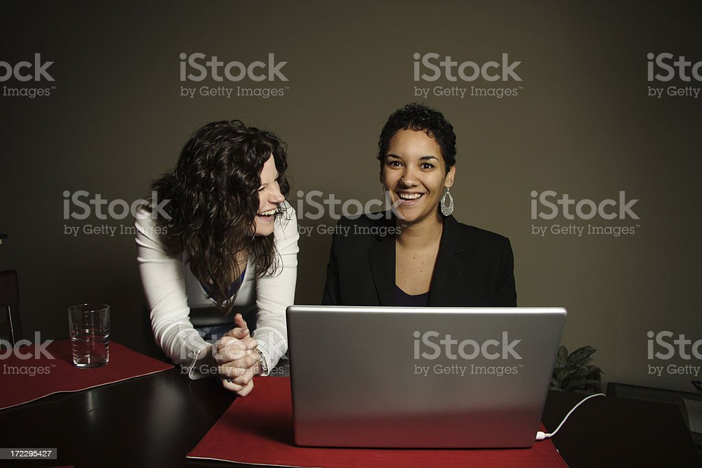 young ladies laughing and typing royalty-free stock photo