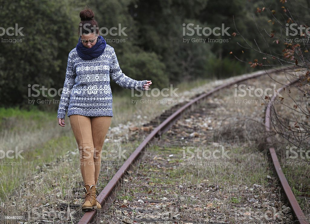 Young lady balancing on the rail road track royalty-free stock photo