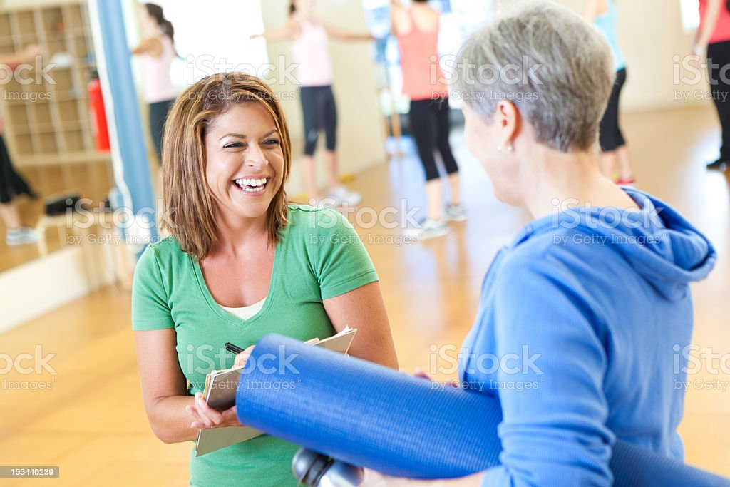 Young lady checking in mature woman into exercise class royalty-free stock photo