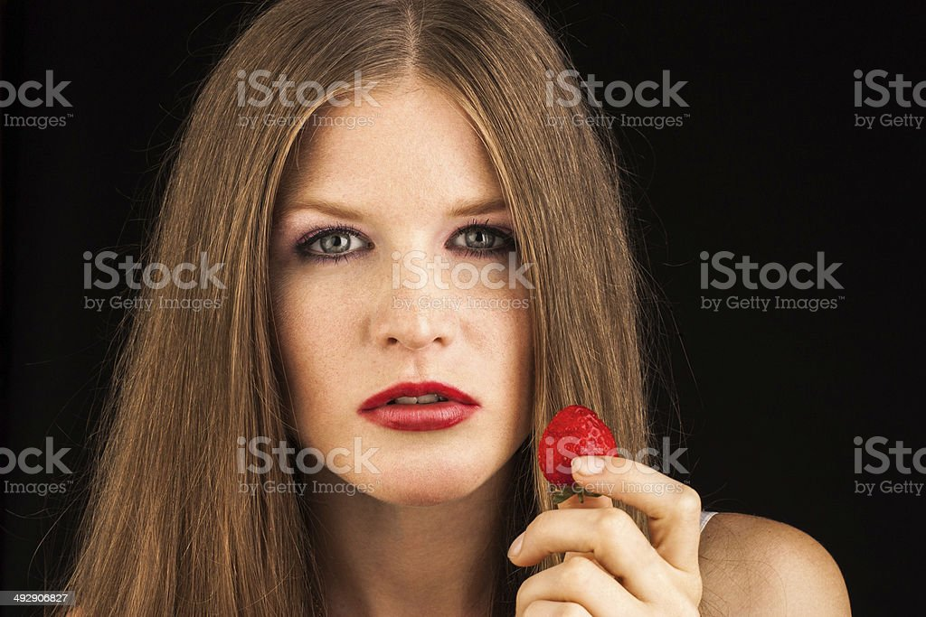 Young lady eating a strawberry royalty-free stock photo