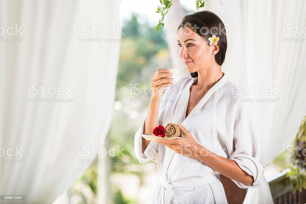 Young lady enjoying her cup of tea after massage stock photo