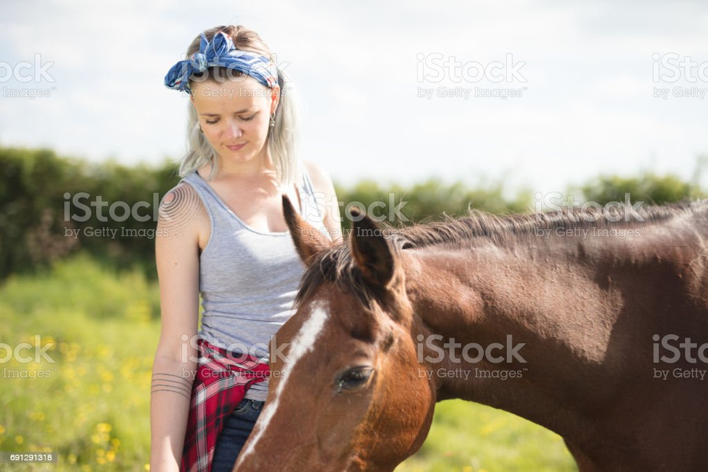 Young lady feeding her horse stock photo