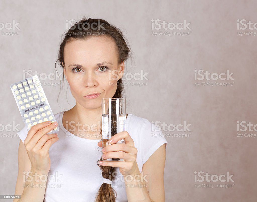 Young lady has a glass of water and pilss stock photo