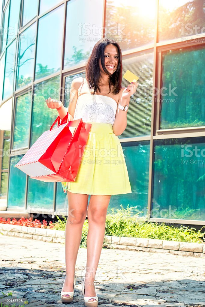 Young lady holding Gold Card while shopping stock photo