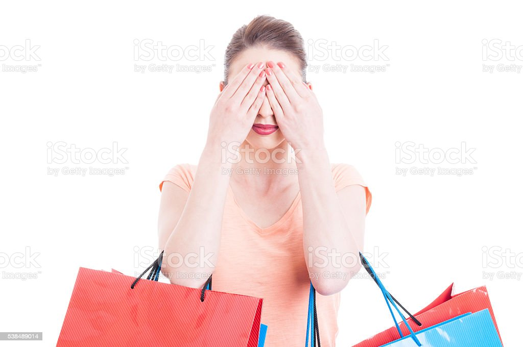 Young lady holding shopping bags making blind gesture stock photo