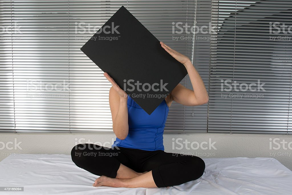 Young lady is holding up a blank black poster board stock photo