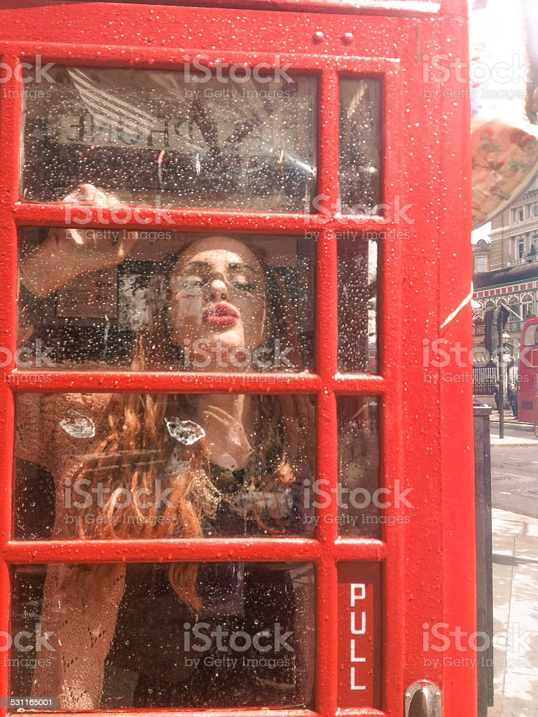 Young lady kissing the glass of a london phone box stock photo