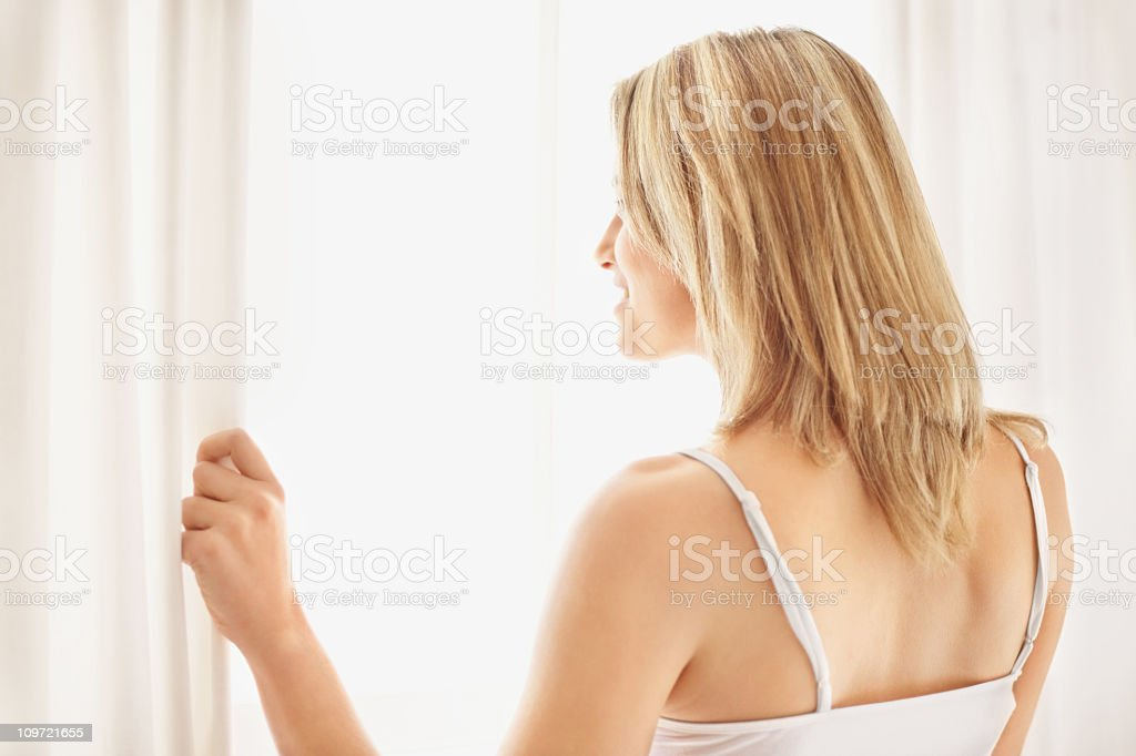 Young lady looking out of window royalty-free stock photo