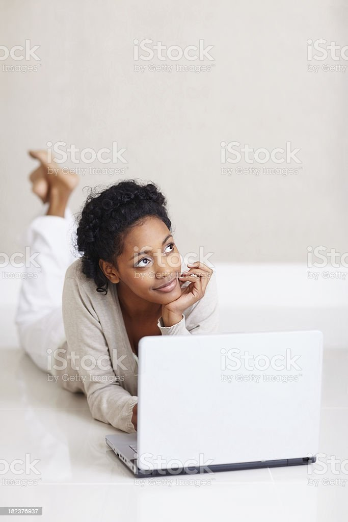 Young lady lying on floor using laptop and looking up royalty-free stock photo