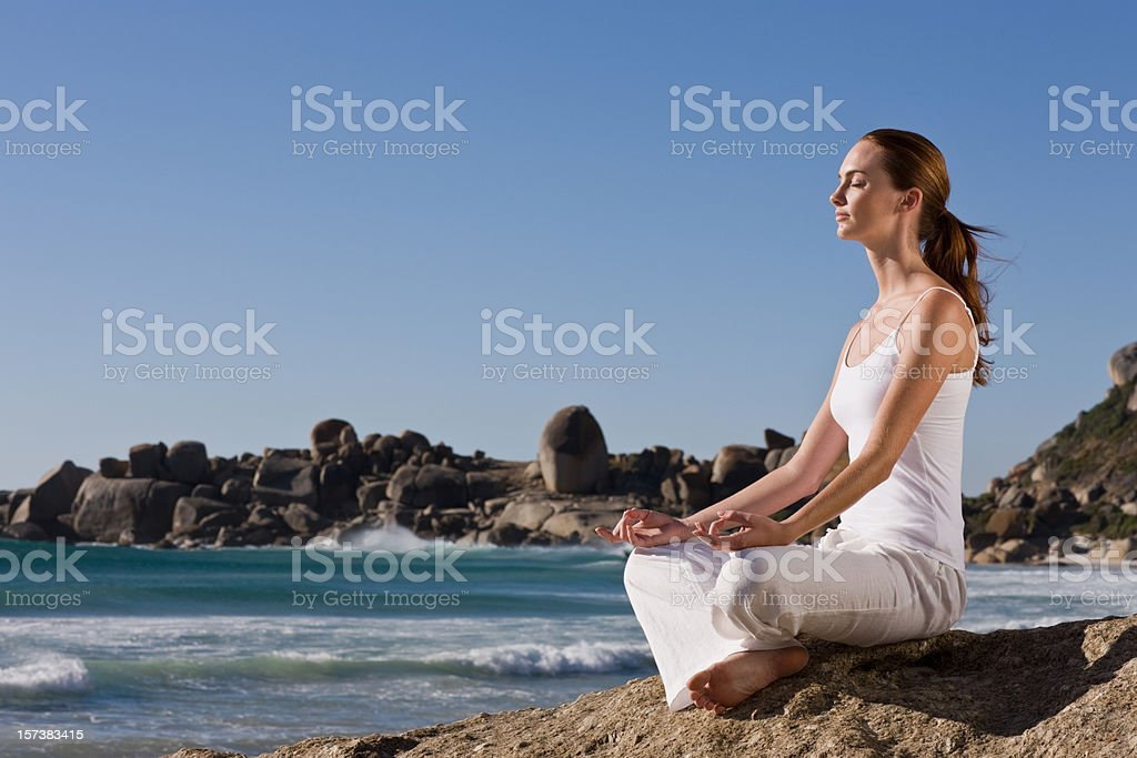 Young lady meditating on rock by sea royalty-free stock photo