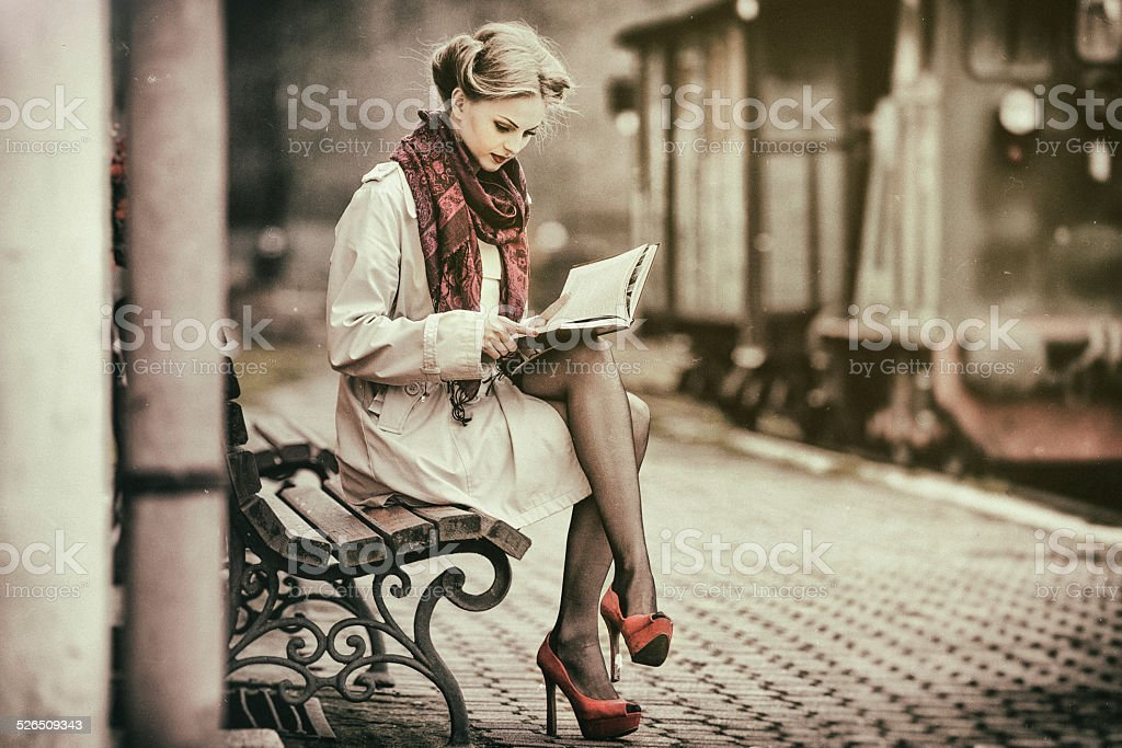Young lady reading book, waiting for a train stock photo