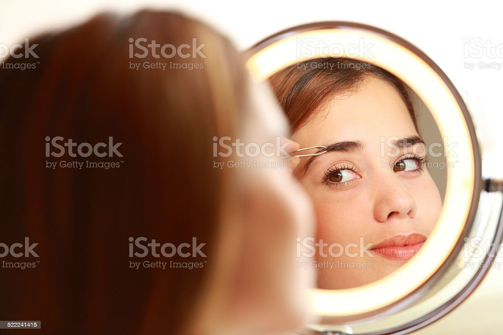Young Lady Removing Eyebrows stock photo