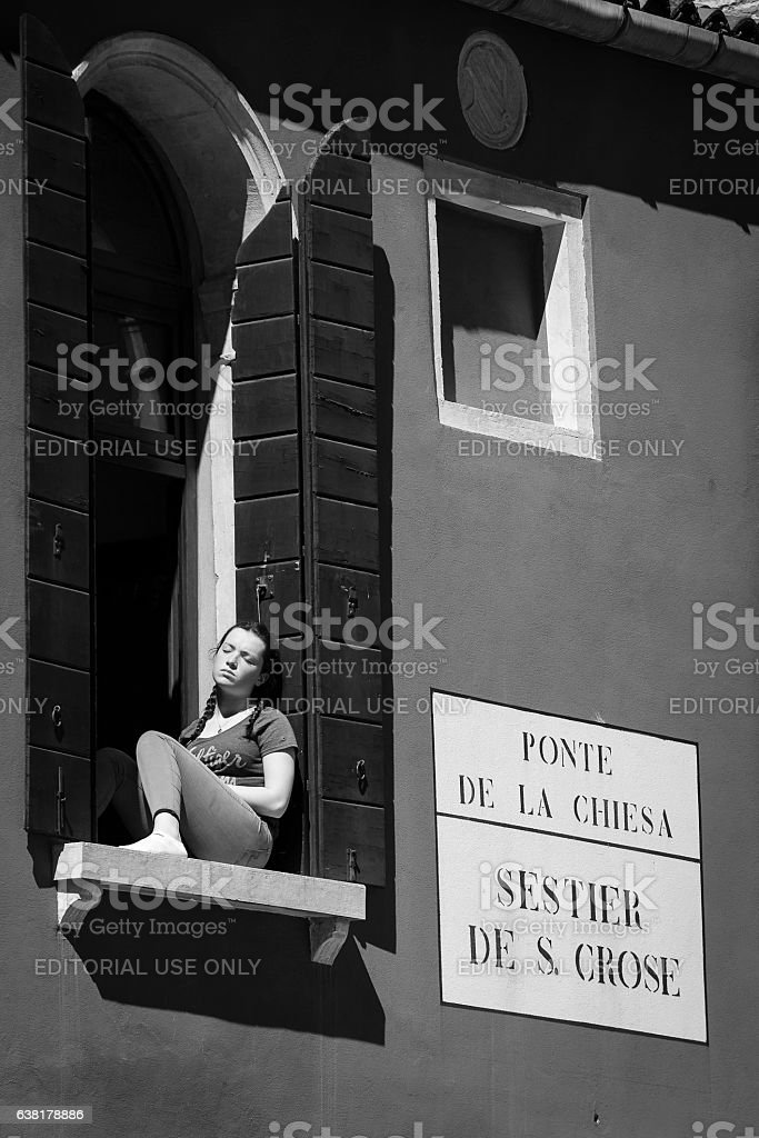 young lady resting under the sun at her window, Venice stock photo
