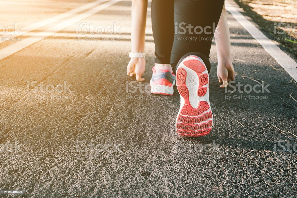 Young lady running on road closeup on shoes. royalty-free stock photo