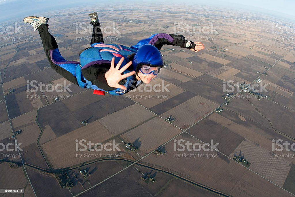 Young lady skydiving whilst mid-air waving to camera royalty-free stock photo
