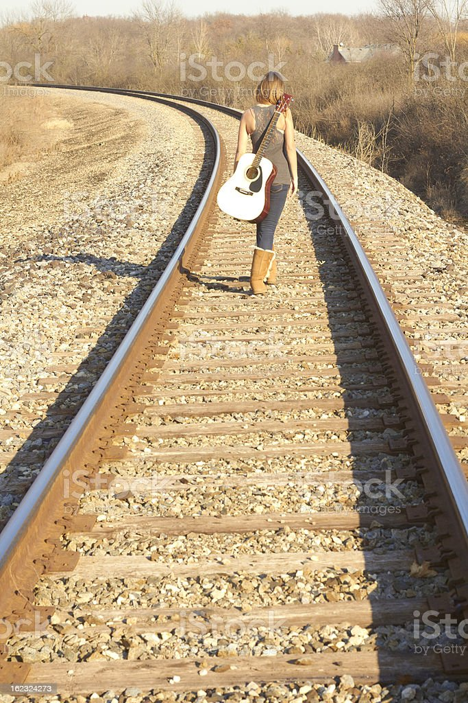 Young Lady Walking On Railroad Tracks With Guitar stock photo