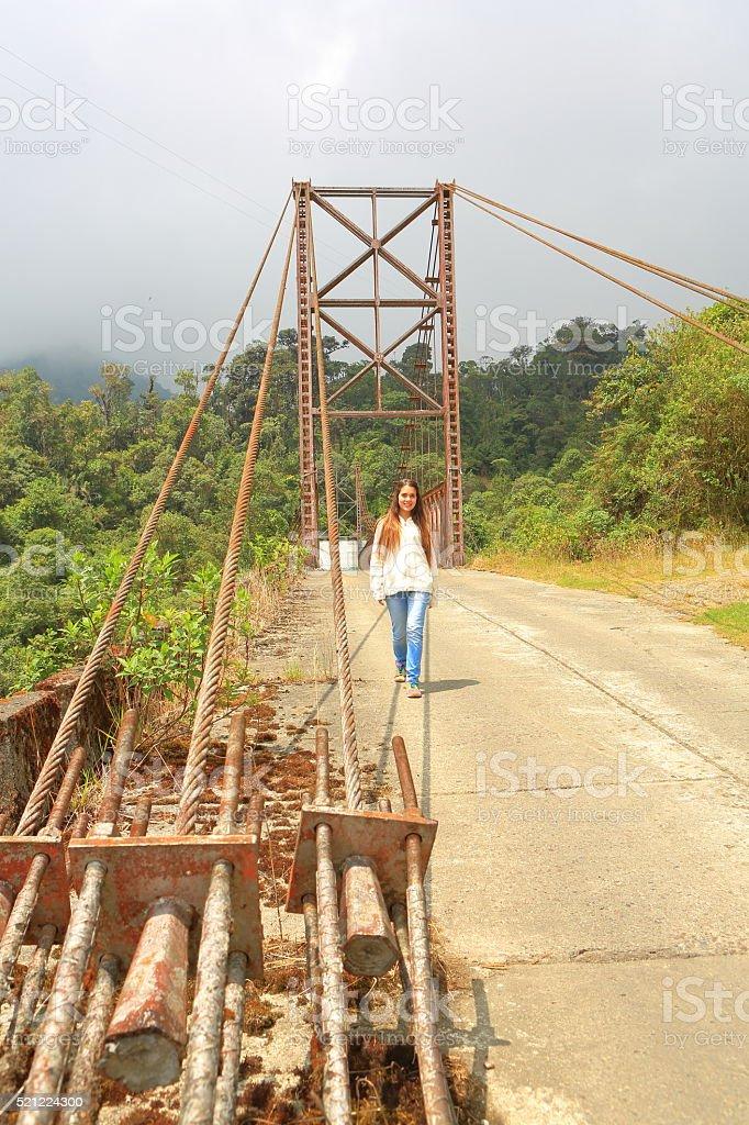 Young Lady Walking Through an old Steel Bridge stock photo