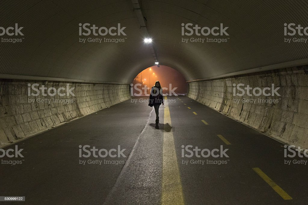 Young lady walks alone trough a tunnel in the night stock photo