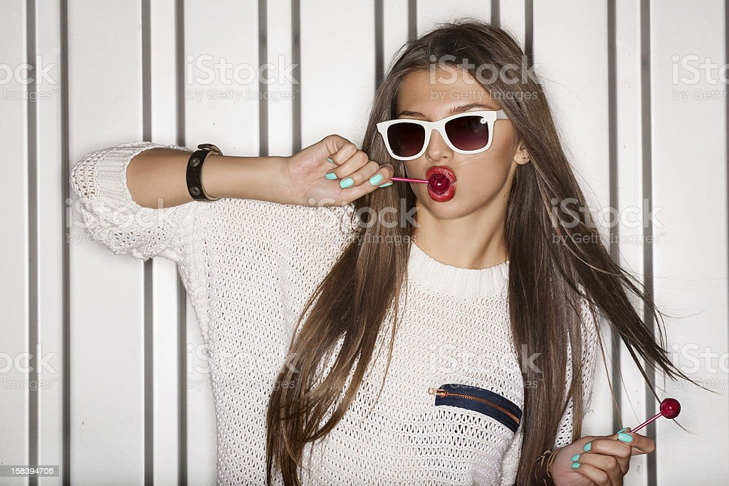 Young lady wearing sunglasses sucking a lollipop stock photo