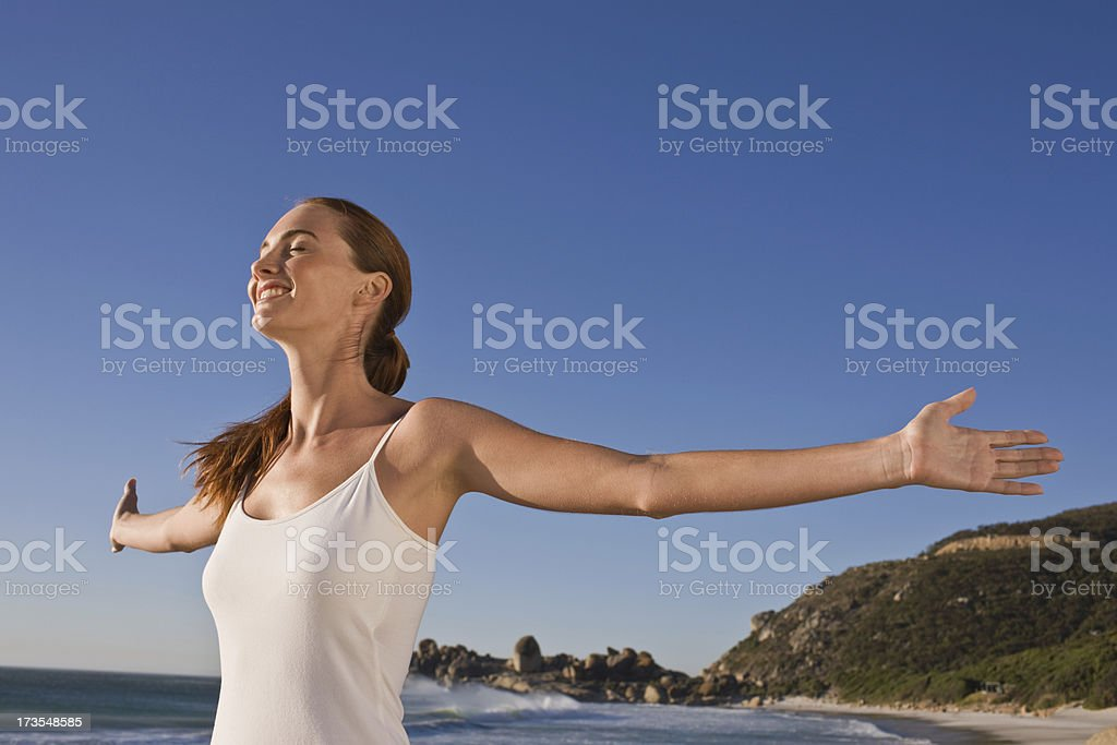 Young lady with arms outstretched standing at beach royalty-free stock photo