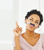 Young lady with pen on mouth gesturing up