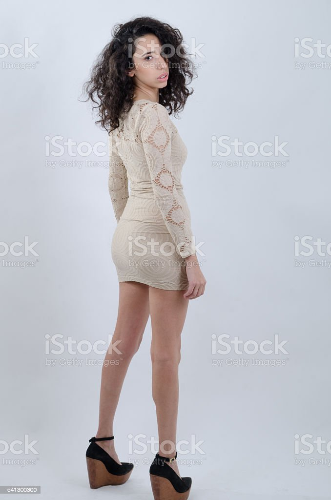 Young latin girl wearing a beige dress looking at camera stock photo