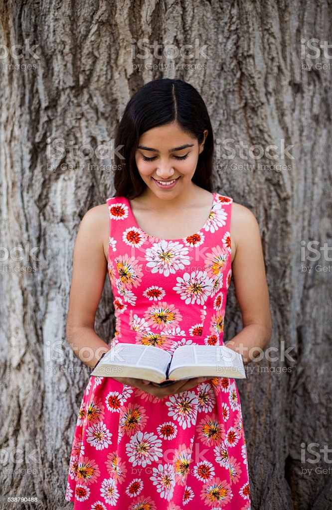 Young Latin lady reading the Bible stock photo
